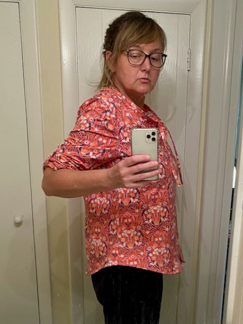 Photo of woman taking selfie in mirror wearing a pink print top.