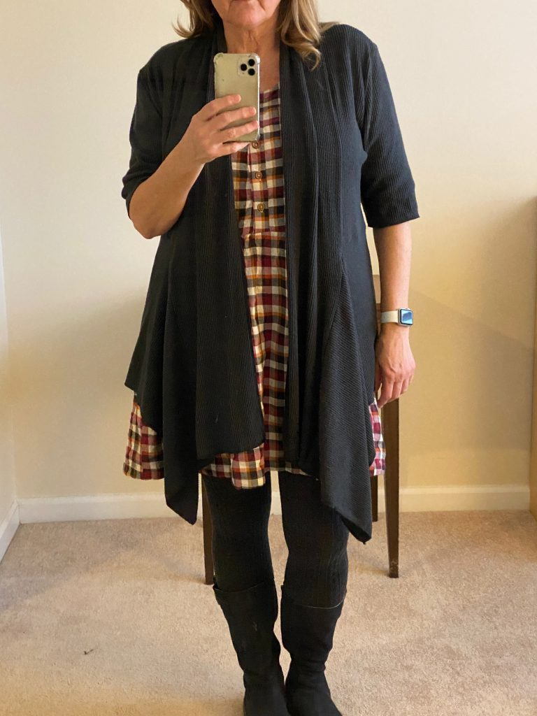 Image of woman wearing open cardigan over a plaid dress